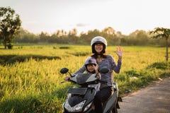 妈妈和她的孩子喜欢乘坐摩托车滑行车 图库摄影