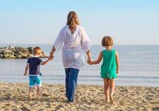 妈妈和她的孩子手拉手走在海滩 免版税库存照片