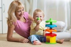 妈妈和她的孩子有五颜六色的逻辑玩具的 获得的家庭在家一起使用的乐趣 免版税图库摄影