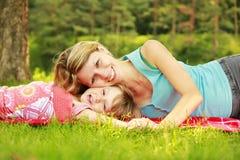 妈妈和她的小女儿在草说谎 免版税库存图片