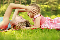 妈妈和她的小女儿在草说谎 库存照片