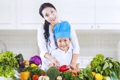 妈妈和厨师男孩在厨房里 免版税库存照片