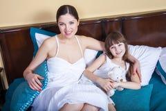 妈妈和她美丽的女孩在床上在早晨,拥抱, 库存照片