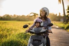 妈妈和孩子喜欢乘坐摩托车滑行车 免版税库存图片