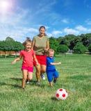 妈妈和孩子在公园踢橄榄球 库存图片