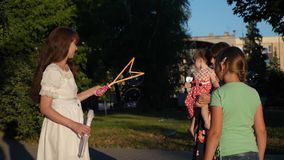妈妈和孩子在城市公园吹泡影 保姆招待少年和一点婴孩平衡的步行的 股票视频