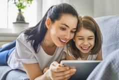 妈妈和孩子有片剂的 免版税库存图片
