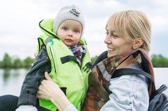 妈妈和小女儿乘在河的小船在一个春日 免版税库存照片