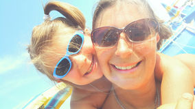 妈妈和小女孩微笑愉快在海滩 免版税库存图片