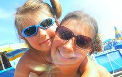 妈妈和小女孩微笑愉快在海滩 库存照片