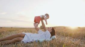 妈妈和愉快地使用在自然的男婴,在领域的母亲采取她的胳膊的婴孩并且放松  股票录像