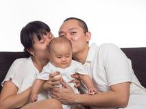 妈妈和爸爸亲吻婴孩 库存图片