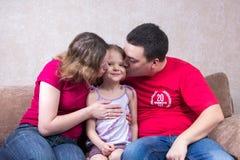 妈妈和爸爸亲吻他们的长沙发的女儿 免版税库存照片