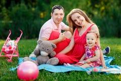 妈妈和爸爸有女儿的格子花呢披肩的在公园 库存照片