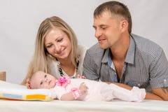 妈妈和爸爸考虑他们的两个月婴孩 库存照片