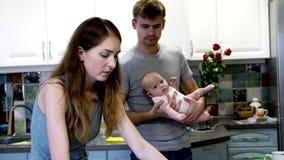 妈妈和爸爸,与一个小孩子一起,在厨房 股票视频