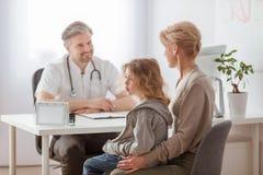 妈妈和病的儿子在英俊的儿科医生的书桌前面 免版税库存照片