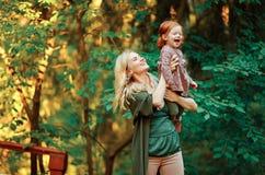 妈妈和红发女儿是参加和微笑对日落  免版税图库摄影
