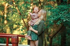妈妈和红发女儿是参加和微笑对日落  库存图片