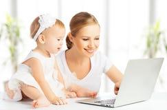 妈妈和婴孩有运转从家的计算机的 免版税库存图片