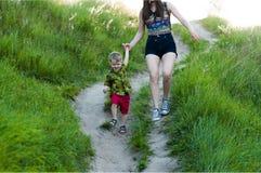 妈妈和他的儿子是在从小山的足迹下 免版税库存照片