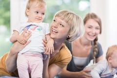 年轻妈妈和他们的小孩母亲和孩子的追猎 图库摄影