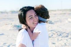 妈妈和doughter在海滩,一起拥抱 库存照片