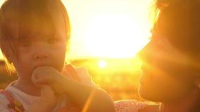 妈妈唱歌曲给一个小愉快的女儿 孩子在母亲的胳膊在a点燃的春天坐在公园 股票视频