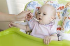 妈妈喂养有匙子的婴孩 库存照片