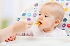 妈妈喂养从匙子的滑稽的婴孩 库存照片