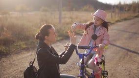 妈妈在一个温暖的秋天晚上教女孩骑自行车 一个愉快的家庭的概念 股票录像