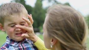 妈妈在从晒斑的儿童的面孔上把奶油放 医疗保健,皮肤防护 股票录像