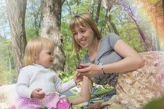 妈妈在使用与他的女儿的一个晴天在绿色公园 免版税库存图片