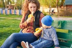 妈妈在公园吃并且喂养她的儿子用在一条长凳的香蕉 E 库存图片