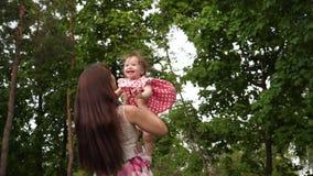 妈妈在公园投掷在空气的婴孩上流,笑和使用与她 股票录像