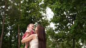 妈妈在公园投掷在空气的婴孩上流,笑和使用与她 股票视频
