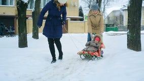 妈妈在冬天拉扯她的一个雪撬的一点婴孩 股票录像