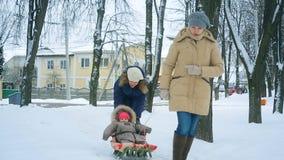 妈妈在冬天拉扯她的一个雪撬的一点婴孩 股票视频