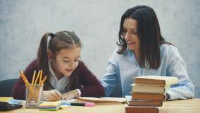 妈妈在厨房里帮助我的女儿做她的家庭作业 妈妈和女儿参与读书 他们在心情 股票视频