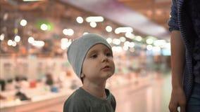 妈妈在商店穿上一个小儿子` s帽子并且与他谈话 股票录像