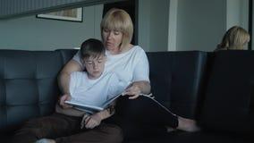 妈妈在客厅帮助我的儿子做家庭作业 一个愉快的家庭的概念 影视素材