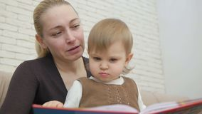 妈妈在客厅读他的小女儿书坐长沙发 影视素材