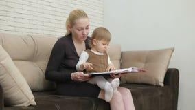 妈妈在客厅读他的小女儿书坐长沙发 股票录像