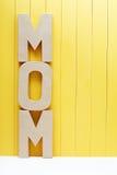 妈妈在黄色木背景的文本信件 免版税库存照片
