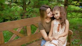 妈妈坐长凳,她有她的膝部的一个小女孩 妇女轻轻地拥抱孩子坐在的一条长凳 股票视频