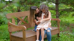 妈妈坐长凳,她有她的膝部的一个小女孩 有儿童游戏的,无忧无虑的笑妇女,获得乐趣坐 股票录像