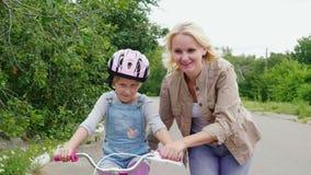 妈妈学会一个女儿骑自行车 她高兴在女孩的第一成功 steadicam射击 股票视频