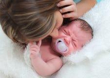 妈妈安慰一个哭泣的婴孩 免版税库存照片