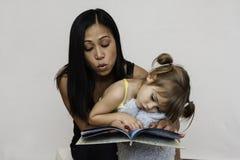 妈妈对三岁的女儿的阅读书 免版税图库摄影