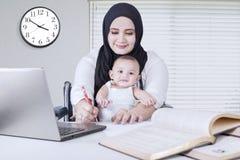 妈妈工作,当举行她的婴孩时 库存照片